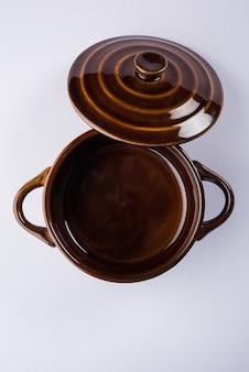 Ciotola o contenitore in ceramica vuota con coperchio o barni, isolata su sfondo semplice