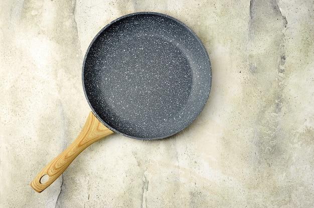Padella in ceramica vuota con manico in legno su una superficie di cemento grigio