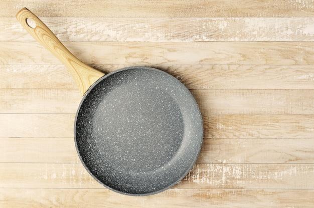 Padella in ceramica vuota con manico in legno su una superficie di legno