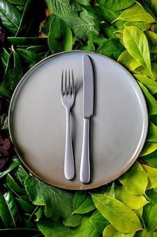 Piatto in ceramica vuoto con coltello e forchetta su sfondo fatto di foglie verdi, sfumatura verde. posto vuoto per il prodotto. concetto di cibo ecologico del menu estivo. layout creativo della natura, vista dall'alto, disposizione piatta