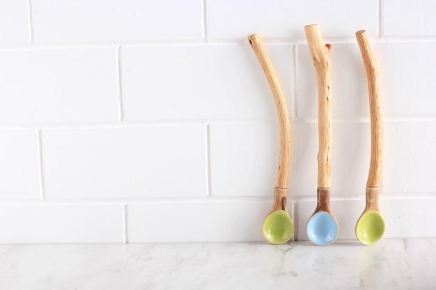 Cucchiai di ceramica vuoti. cucchiai artigianali indonesiani con manico in legno rustico naturale e colore pastello. copia spazio per il testo