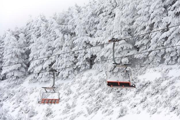 Seggiovia vuota nel paesaggio di montagna ricoperta di neve. spazio per il testo.