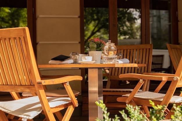 Sedie vuote e utensili da tè sul tavolo del caffè