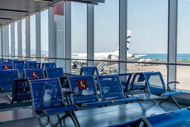 Sedie vuote con un segno di ascolto limitato nell'edificio dell'aeroporto