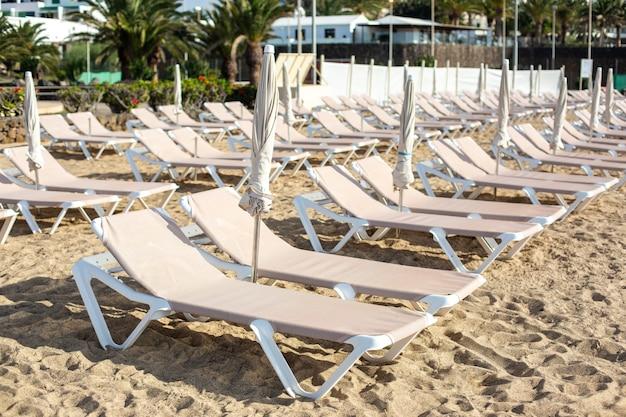 Chaise-lounge vuote sulla spiaggia nella città di costa teguise. isola di lanzarote, spagna.