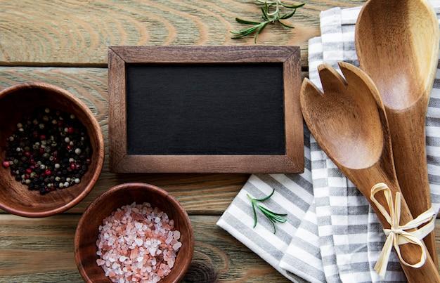 Lavagna vuota e utensili da cucina con spezie su un vecchio tavolo di legno