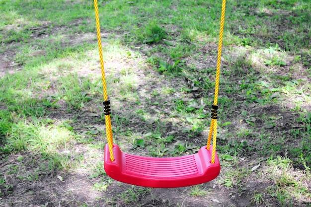Altalena in plastica rossa per bambini vuoti su corde gialle. nessuno. concetto di infanzia e solitudine.