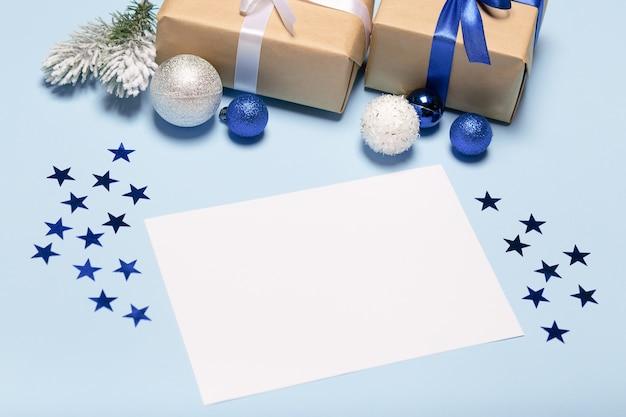 Cartolina di natale vuota su sfondo blu, natale blu con decorazioni, confezione regalo e palline.