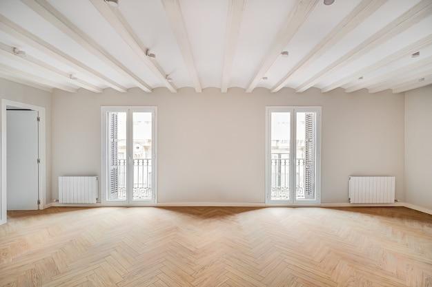 Stanza vuota e pulita in un appartamento ristrutturato con pavimento in legno e due balconi luminosi interni immobiliari