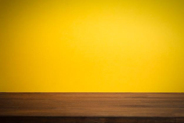 Sfondo giallo pulito vuoto con tavolo in legno.
