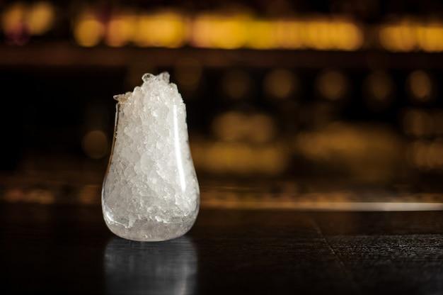 Bicchiere da cocktail vuoto riempito con molto ghiaccio sul bancone del bar in sfondo sfocato della barra