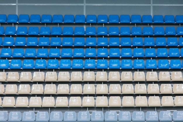 Posti a sedere di plastica colorati vuoti sulla piattaforma di osservazione del complesso di piscina al coperto prima della concorrenza