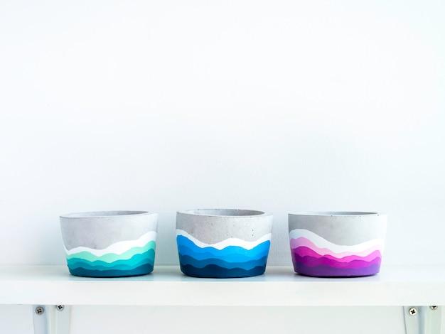 Vasi di cemento rotondi fai da te colorati vuoti su uno scaffale di legno bianco sul muro bianco con spazio per le copie tre fioriere in cemento dipinte a colori unici.