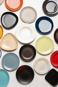 Piatti in ceramica colorati vuoti in gruppo su sfondo bianco, vista dall'alto