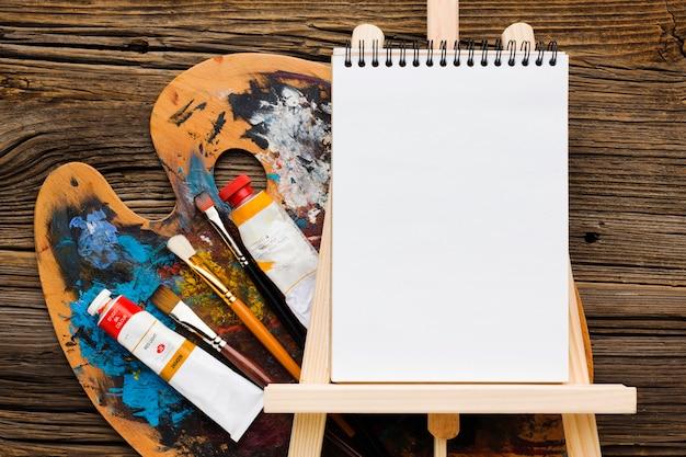 Blocco note e vernice vuoti dello spazio della copia