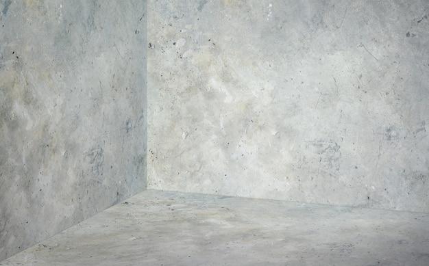 Stanza d'angolo vuota con il fondo grigio del pavimento e del muro di cemento