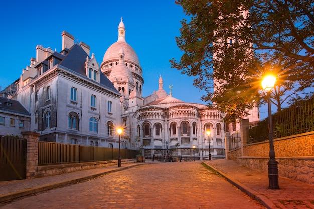 Strada vuota e accogliente e la basilica del sacro cuore durante l'ora blu mattutina, quartiere montmartre a parigi, francia