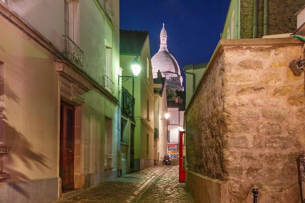 Strada vuota e accogliente e la basilica del sacro cuore di notte, quartiere montmartre a parigi, francia