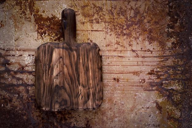 Tagliere di legno vuoto su uno sfondo di metallo arrugginito. vista dall'alto con copia spazio