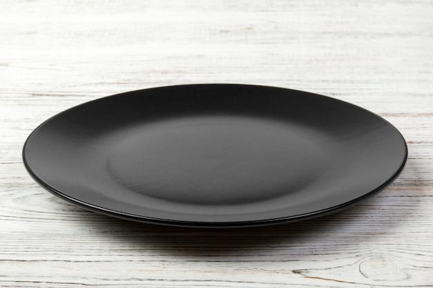 Piatto opaco scuro vuoto per la cena su fondo di legno bianco