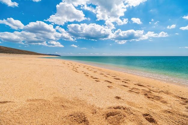 Spiaggia dorata vuota e deserta con sabbia a conchiglia e mare azzurro cristallino.