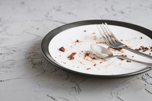 Piatto sporco vuoto con un cucchiaio e una forchetta di briciole di dessert su fondo di cemento