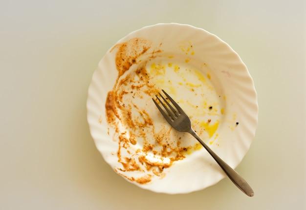 Piatto di porcellana sporco vuoto con una forchetta dopo la pasta alla bolognese su una scrivania grigia