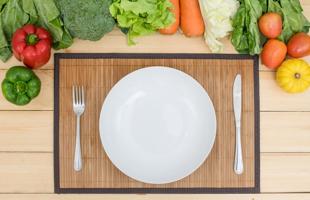 Il piatto vuoto, la gente e il coltello intorno con i pomodori, i peperoni, le carote, la lattuga di zucca e la verdura verde