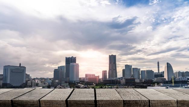 Tavola di legno vuota dell'esposizione con lo spazio della copia per il contesto di pubblicità con il fondo dell'orizzonte di yokohama della città moderna