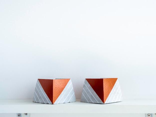 Vasi vuoti in cemento fai da te, a forma di piramide su uno scaffale di legno bianco su parete bianca con spazio per le copie due uniche fioriere in cemento verniciato color rame.