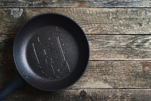 Padella vuota sopra fondo di legno. vista dall'alto, copia dello spazio. sfondo culinario grigio scuro. uomo che versa olio da cucina sulla padella.