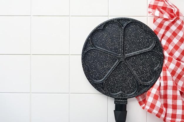 Padella vuota nera, padella con rivestimento antiaderente in pietra per cuocere frittelle a forma di cuori e ingredienti per la colazione su sfondo grigio tavolo in cemento. colazione per san valentino. vista dall'alto.