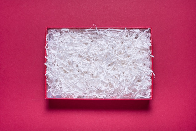 Confezione regalo vuota con riempitivo di carta su sfondo rosso