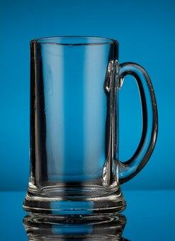 Bicchiere da birra in vetro vuoto su sfondo blu
