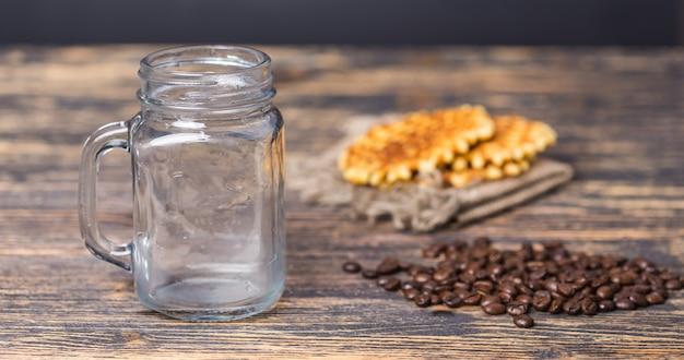 Bicchiere vuoto e chicchi di caffè sullo sfondo.