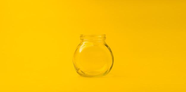 Barattolo di vetro vuoto su sfondo giallo con spazio libero