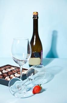 Bicchieri vuoti con scatola di cioccolatini e bottiglia