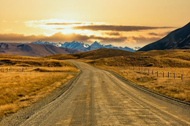 Svuotare la ghiaia strada sterrata che si snoda attraverso il paesaggio rurale di hakatere conservation park negli altopiani di ashburton con lo sfondo delle alpi del sud