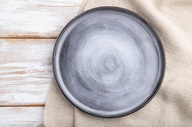 Piatto in ceramica grigio vuoto su fondo di legno bianco e tessuto di lino. vista dall'alto, da vicino, laici piatta.