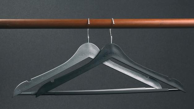 Gruccia per vestiti di plastica grigia vuota che appende su una parete scura. accessori e articoli per riporre i vestiti.