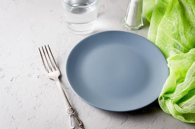 Piatto grigio vuoto che serve per la cena e posate su sfondo grigio cemento.