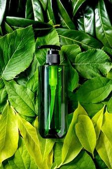 Bottiglia di plastica verde vuota per sapone su sfondo fatto di foglie verdi, sfumatura verde. presentazione del prodotto cosmetico ecologico. posto per etichetta. copia spazio. layout creativo della natura, distesi piatti.
