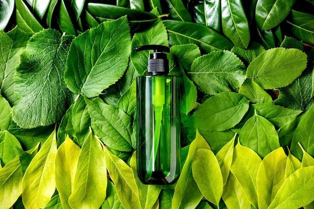 Bottiglia di plastica verde vuota per sapone su sfondo fatto di foglie verdi, sfumatura verde. presentazione del prodotto cosmetico ecologico. posto per etichetta. copia spazio. layout creativo della natura, vista dall'alto.
