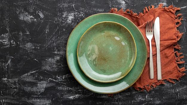 Piatto verde vuoto servito con coltello, forchetta e tovagliolo. piastra modello mockup per cena di lusso con spazio copia sulla vista del piano d'appoggio in cemento nero scuro. banner web lungo.