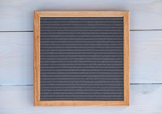 Lavagna vuota in feltro grigio su sfondo di legno naturale