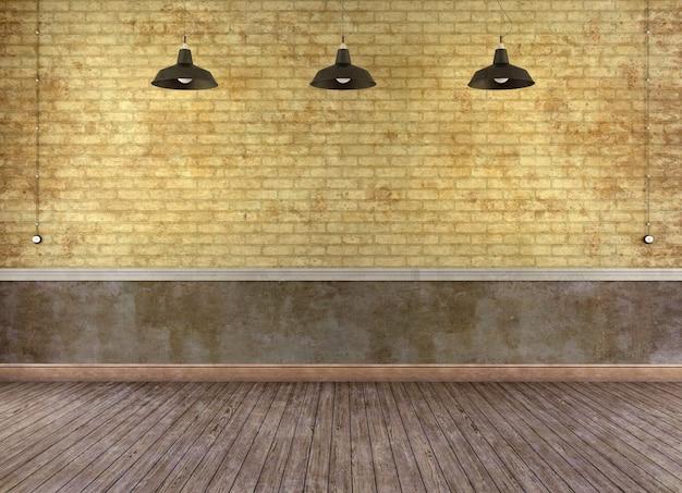 Stanza vuota del grunge con il muro di mattoni