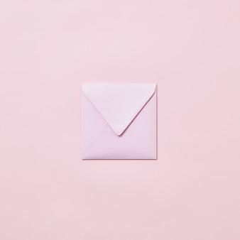 Busta fatta a mano vuota per carta di congratulazioni su uno sfondo rosa chiaro con spazio di copia.