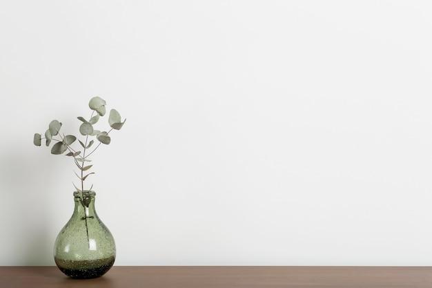 Tavola di legno vuota del fondo della tavola dello scrittorio domestico con un vaso e una pianta contro una parete bianca