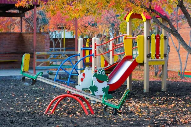 Parco giochi per bambini vuoto in autunno con fogliame rosso