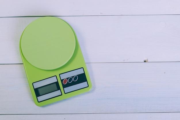 Bilancia da cucina vuota su un tavolo di legno.